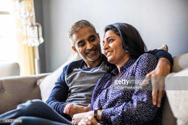 husband and wife embracing on couch - married stock pictures, royalty-free photos & images