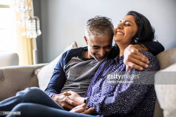 husband and wife embracing on couch - diversity stock pictures, royalty-free photos & images