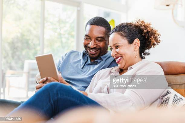 husband and wife enjoy using digital tablet during coronavirus lockdown - mid adult stock pictures, royalty-free photos & images