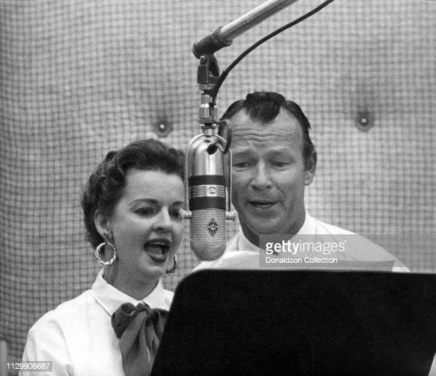 Husband and wife entertainers Roy Rogers and Dale Evans record in the studio at a vintage microphone in 1958.