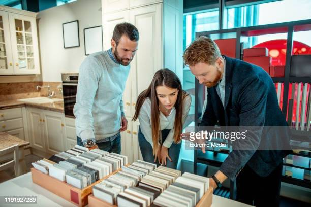 husband and wife going over some tile samples with a seller in a home improvement store - media_(communication) stock pictures, royalty-free photos & images