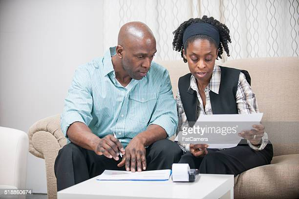 husband and wife going over their personal finances - 1040 tax form stock photos and pictures