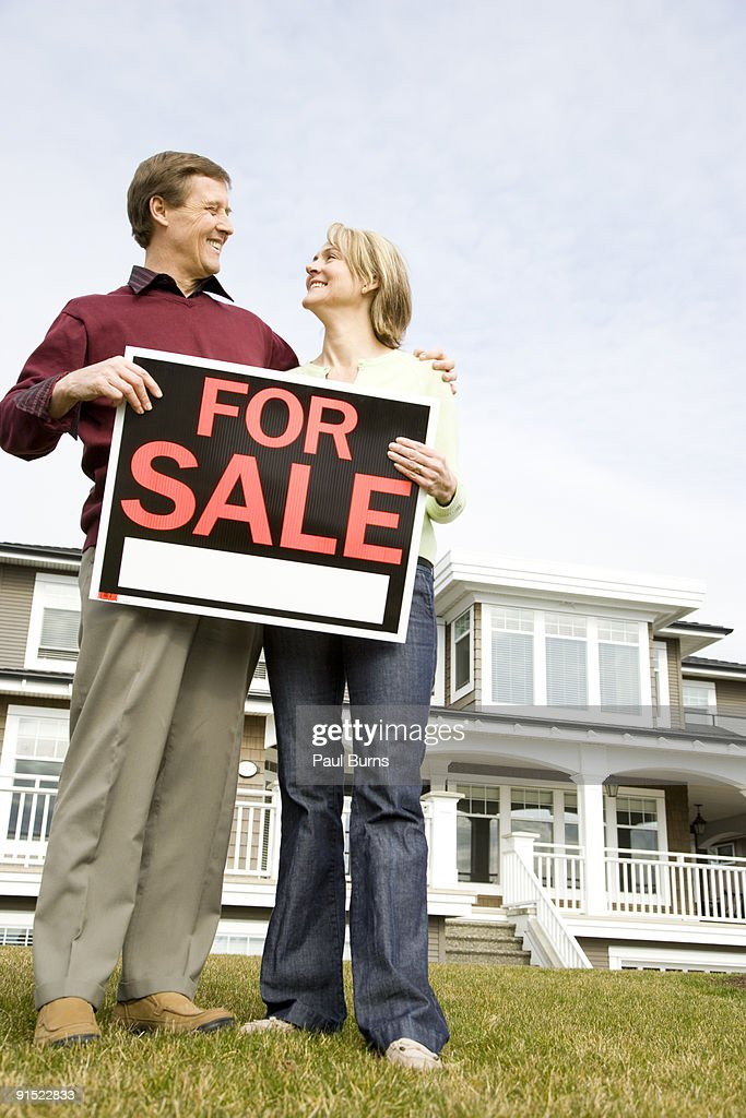 Husband and wife holding 'FOR SALE' sign : Foto de stock