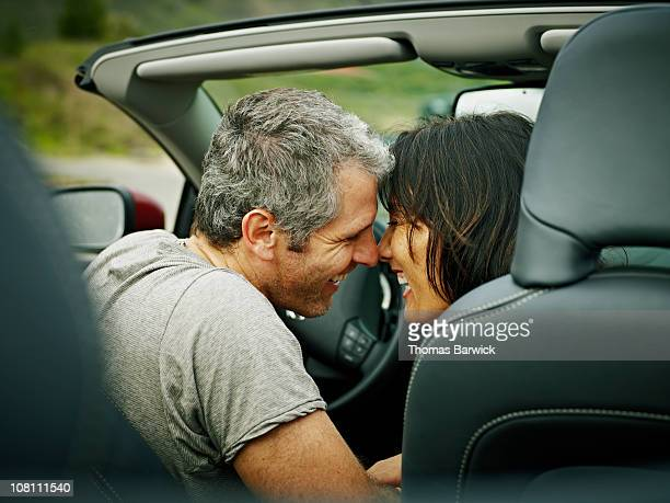 Husband and wife in convertible touching noses