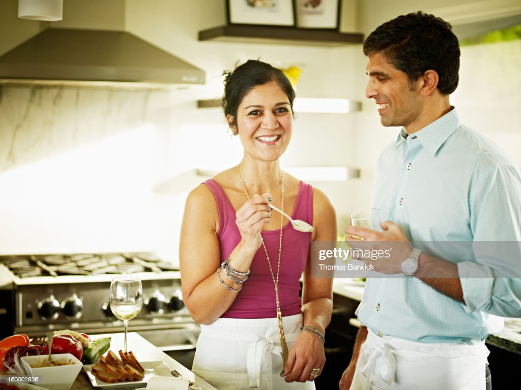 Husband and wife in kitchen preparing food : Stock Photo