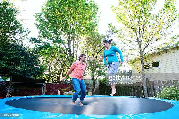 Husband and wife jumping on trampoline