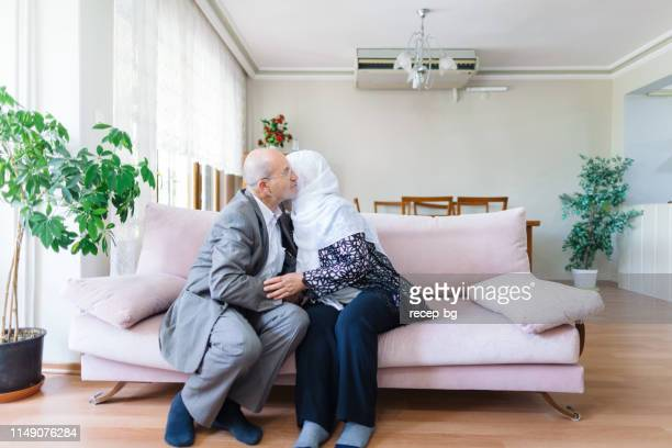 husband and wife kissing each other for celebrating eid al-fitr (end of ramadan) - eid al adha stock pictures, royalty-free photos & images