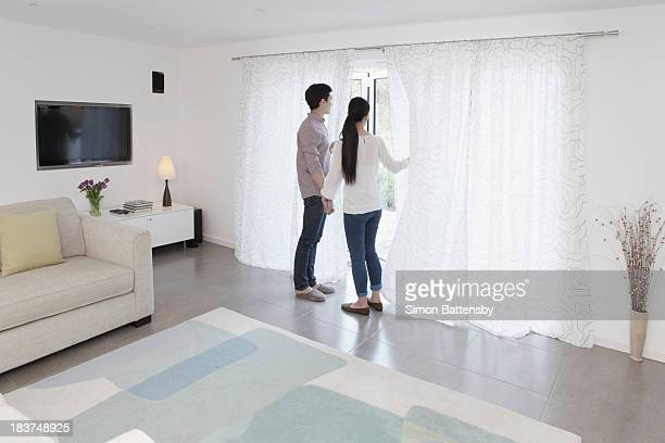 Husband and wife looking out of glass door
