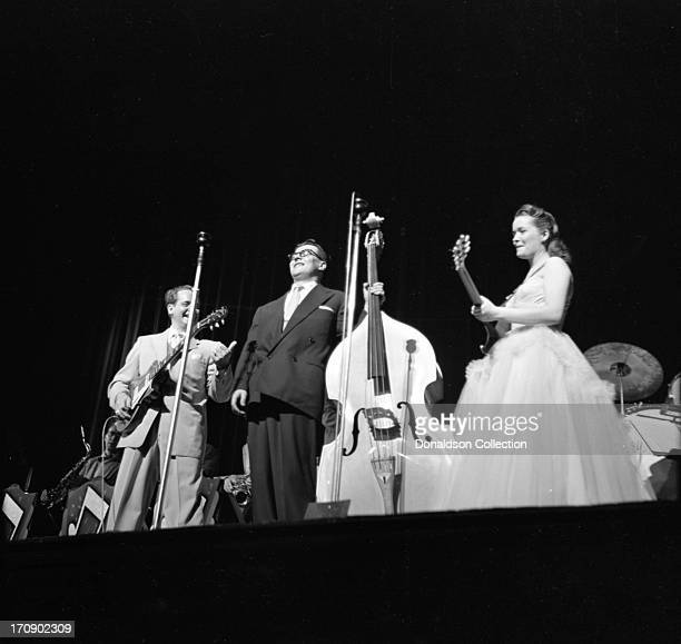 Husband and wife musical team Les Paul and Mary Ford perform onstage with Les Paul electric guitars and an upright bass player at the New York...