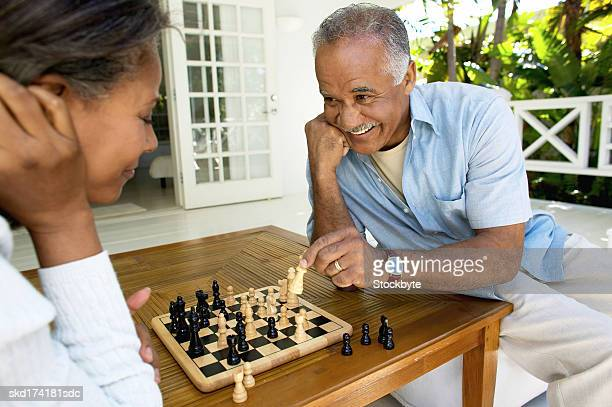 husband and wife playing chess - playing chess stock pictures, royalty-free photos & images