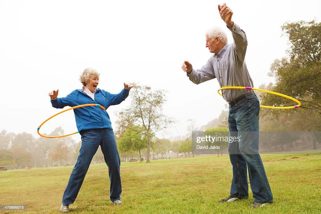 Husband and wife playing hula hoop in the park : Stock Photo