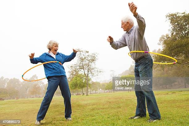 husband and wife playing hula hoop in the park - young at heart stock pictures, royalty-free photos & images
