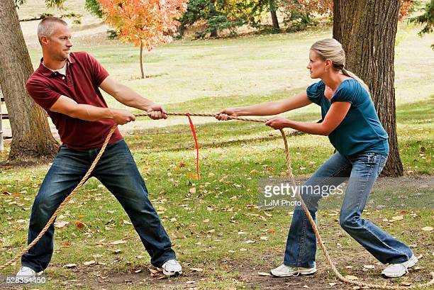 Husband And Wife Playing Tug Of War In A Park; Edmonton Alberta Canada