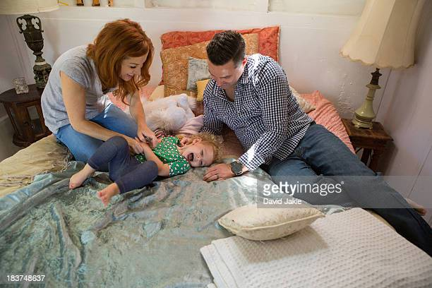 Husband and wife playing with child