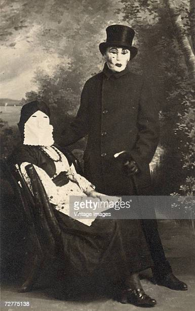 A husband and wife pose in costume for a portrait by M Thomas before a masquerade ball Shamokin Pennsylvania 1910s The wife sits and wears fortune...
