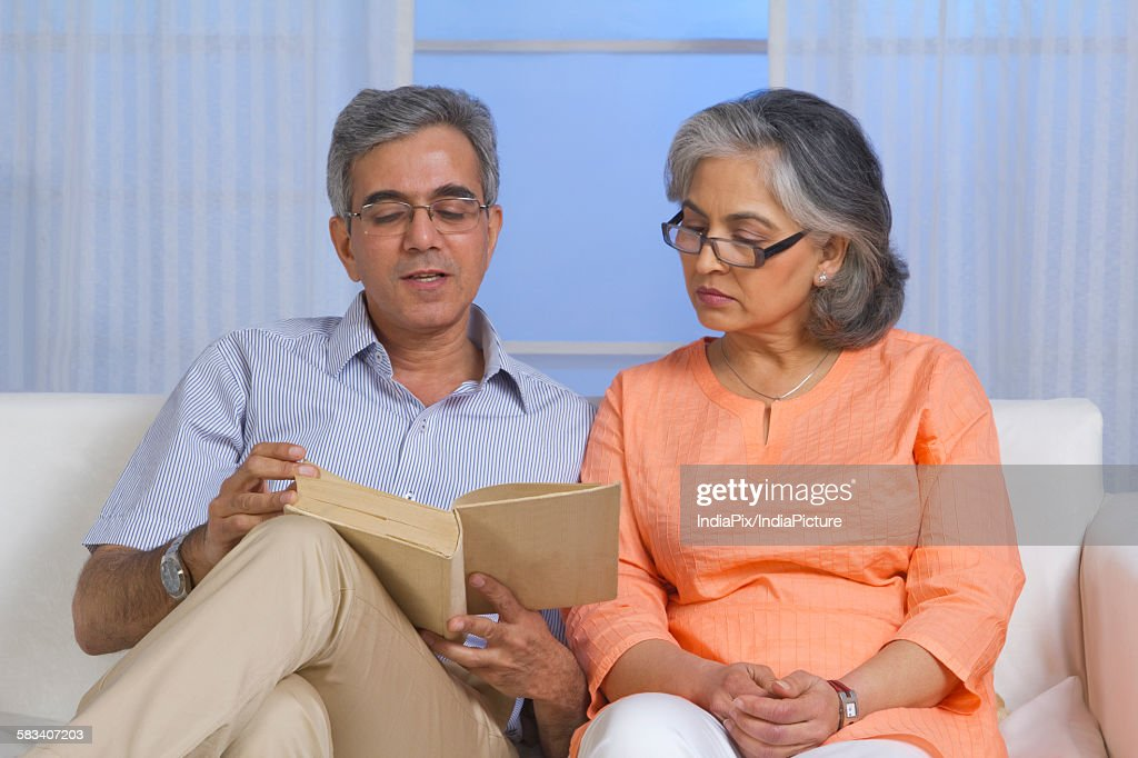 Husband and wife reading a book : Stock Photo