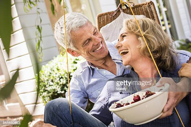 Husband and wife relaxing with bowl of cherries on hammock
