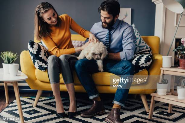 Husband and wife sitting in sofa with their dog