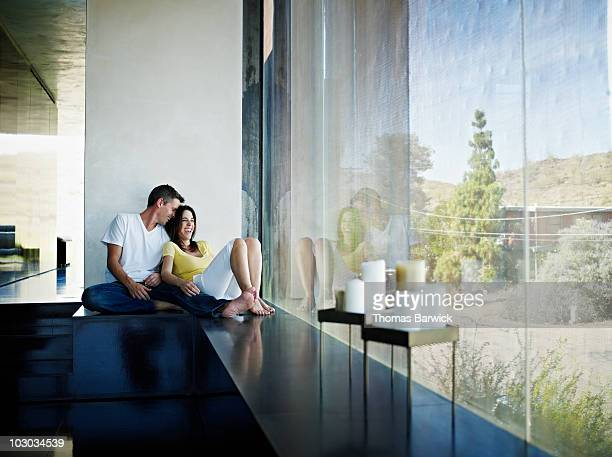 Husband and wife sitting near window of home