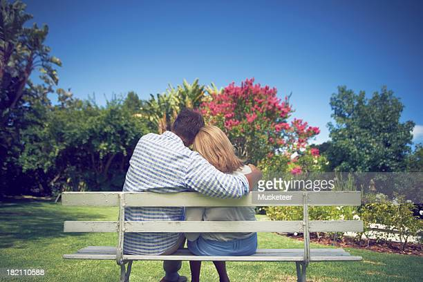 Husband and wife sitting on a bench in the park