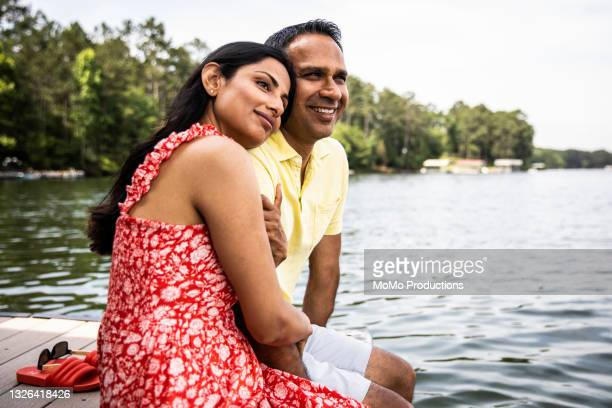 husband and wife sitting on dock at lake - sleeveless dress stock pictures, royalty-free photos & images