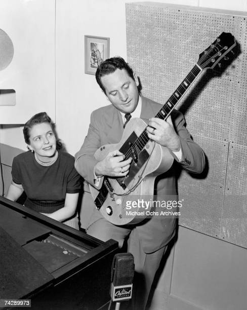 Husband and wife songwriting duo Les Paul Mary Ford perform on electric guitar and piano at a Capitol Records microphone in circa 1952