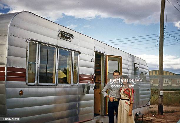 Husband and wife stand beside of their motor home
