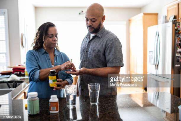 husband and wife taking vitamins at home - moving activity stock pictures, royalty-free photos & images