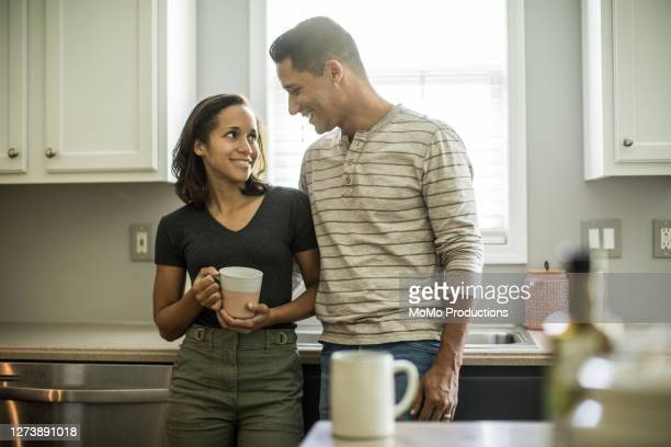 husband and wife talking in kitchen - black hair stock pictures, royalty-free photos & images