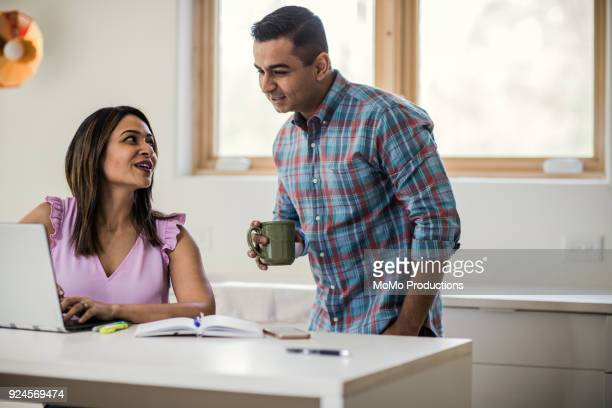 husband and wife using laptop in kitchen - husband stock pictures, royalty-free photos & images