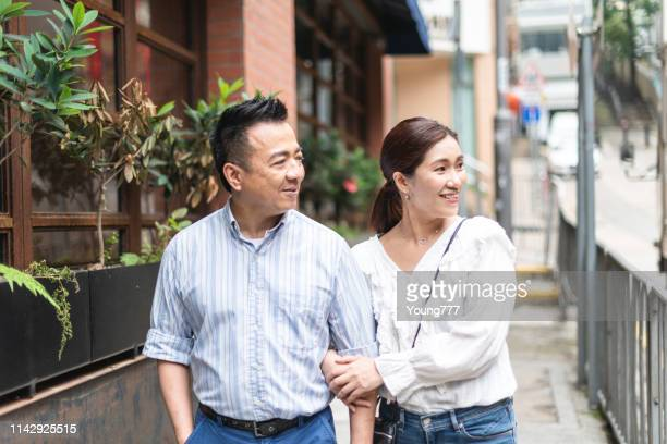 husband and wife walking on the street - mid adult couple stock pictures, royalty-free photos & images