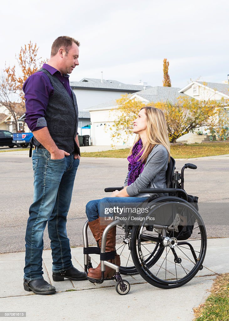 Husband and wife with disability spending time together outdoors : Stock Photo