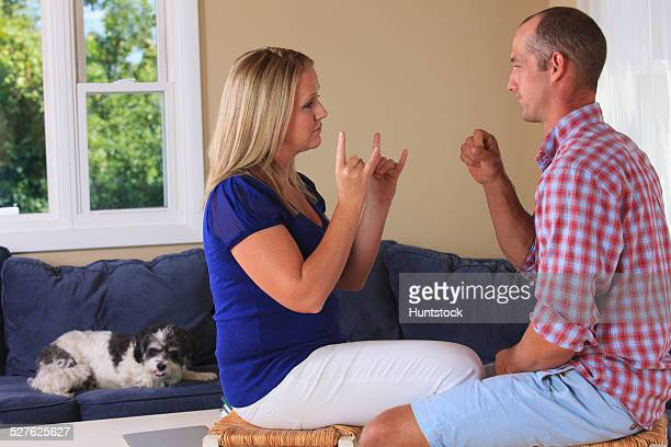 Husband and wife with hearing impairments signing camping in American sign language