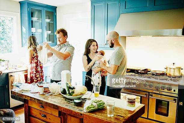 Husband and wife with newborn baby in kitchen