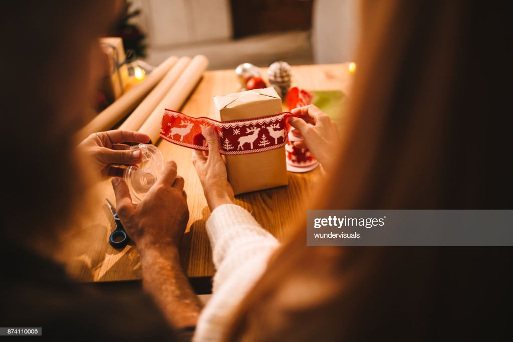 husband and wife wrapping christmas presents for the family stock photo
