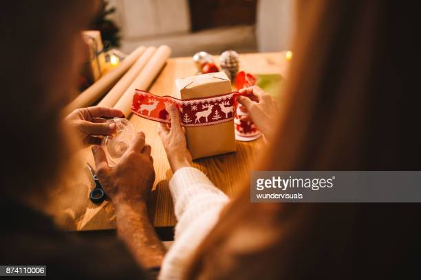 husband and wife wrapping christmas presents for the family - boyfriend stock pictures, royalty-free photos & images