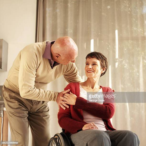 husband bending down to talk to wife who is sitting in a wheelchair