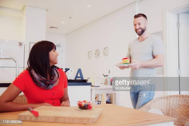 夫は妻にキャンドルとケーキのスライスをもたらします - 1周年 ストックフォトと画像