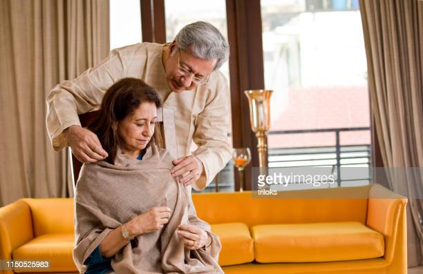 husband comforting old ailing wife at home - husband stock pictures, royalty-free photos & images