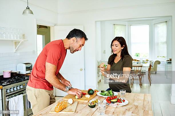 husband cooking for pregnant wife - mid volwassen koppel stockfoto's en -beelden