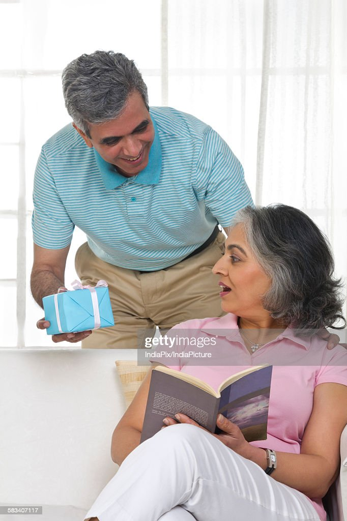 Husband giving a gift to his wife : Stock Photo