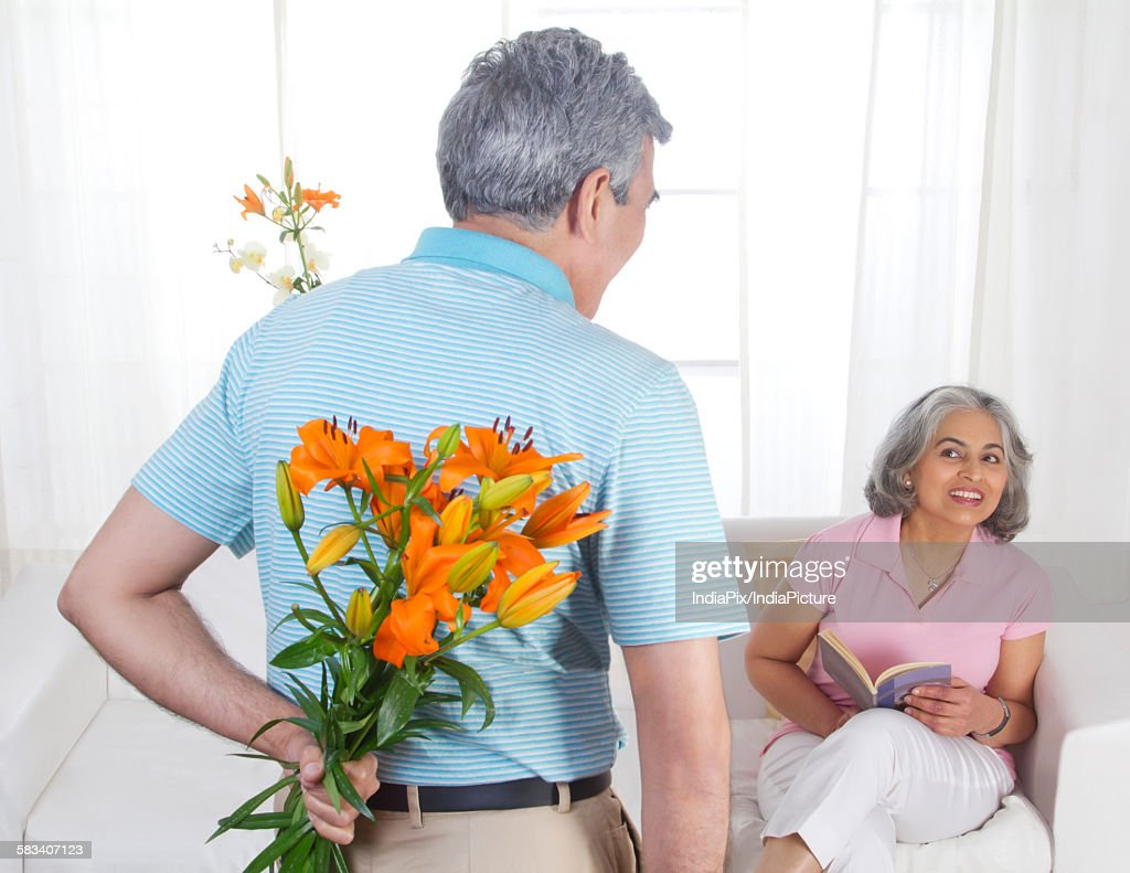 Husband giving flowers to his wife : Stock Photo