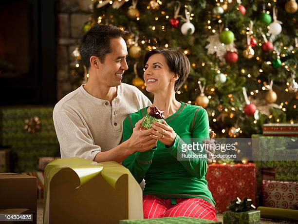 husband giving his wife a present on christmas - orem utah stock pictures, royalty-free photos & images