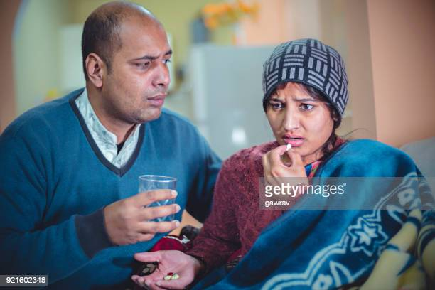 husband giving medicine to his ill wife. - medical condition stock pictures, royalty-free photos & images