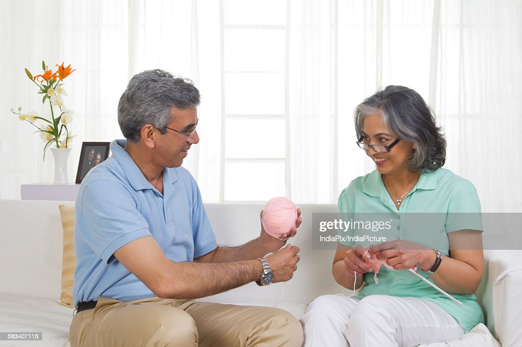 Husband helping while his wife is knitting : Stock Photo