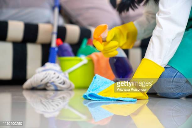 husband housekeeping and cleaning concept, happy young  woman in blue rubber gloves wiping dust using a spray and a duster while cleaning on floor at home - sweeping stock pictures, royalty-free photos & images