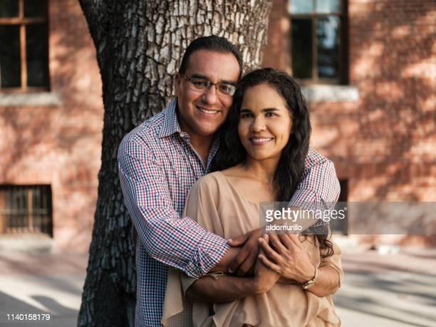 een man knuffelen zijn vrouw uit de rug en simiing - latijns amerikaanse en hispanic etniciteiten stockfoto's en -beelden