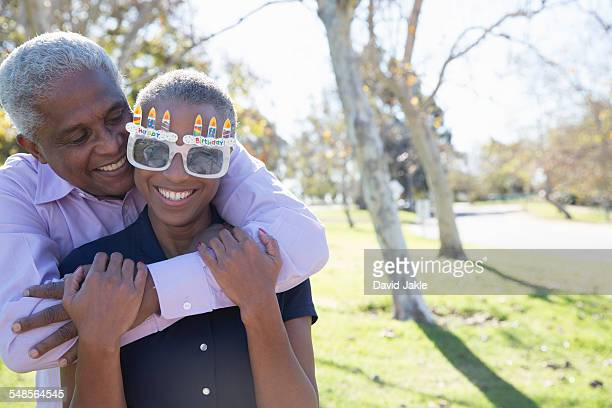 Husband hugging wife wearing party glasses, Hahn Park, Los Angeles, California, USA