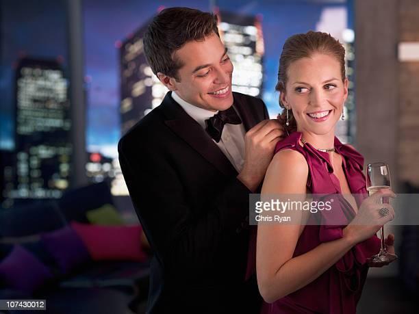 Husband in tuxedo fastening elegant wifes necklace