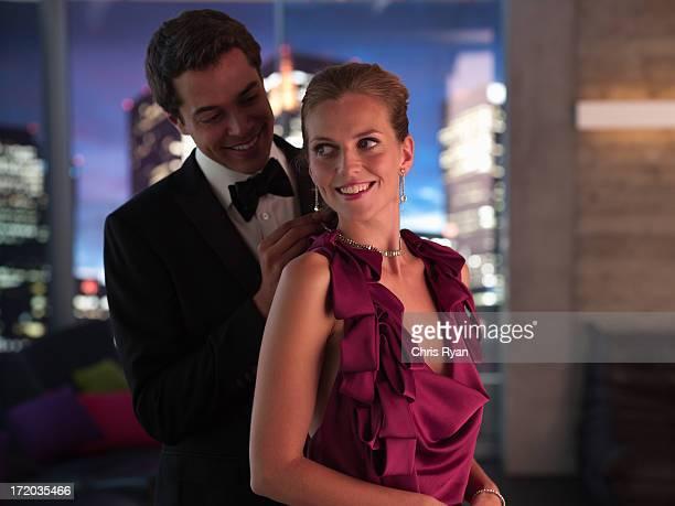 Husband in tuxedo fastening elegant wife's necklace